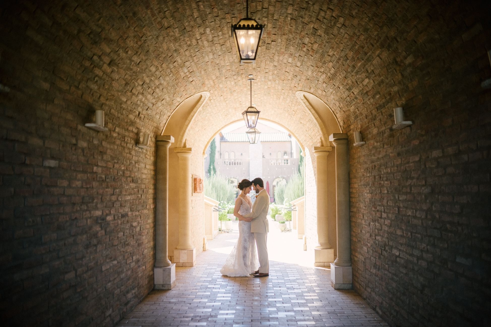 Bride and groom stand face to face under a stone archway