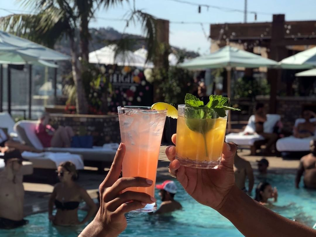 2 cocktails held up in the rooftop pool at Dream Hollywood LA