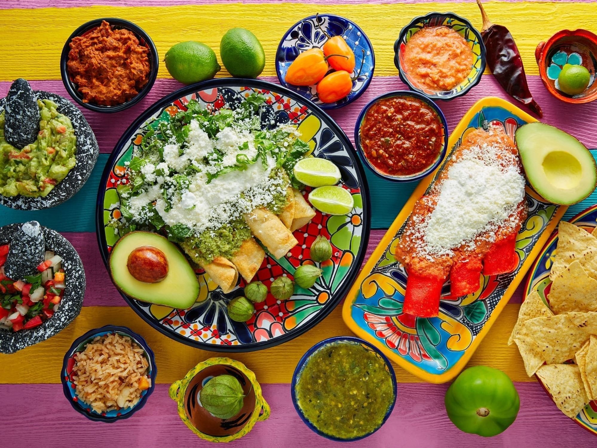 Colorful table with mexican food including enchildas and salsa