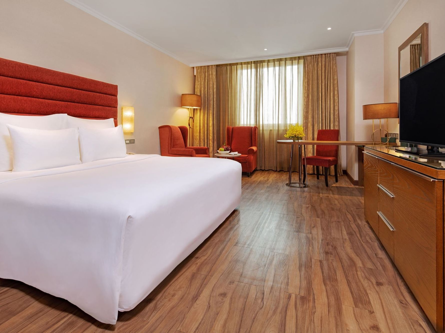 spacious hotel room with wood and red cushion furnishings