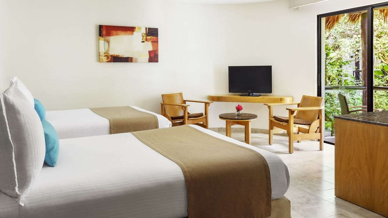 Two beds and TV in Superior room at The Reef Playacar