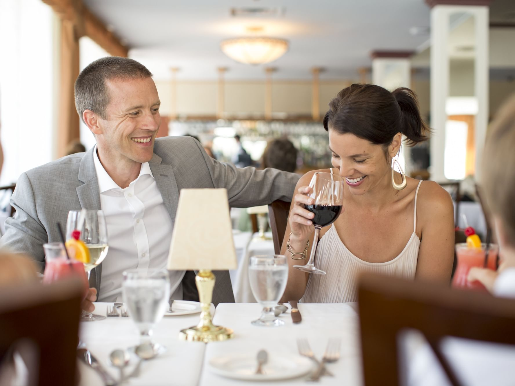 man and woman laughing and drinking wine