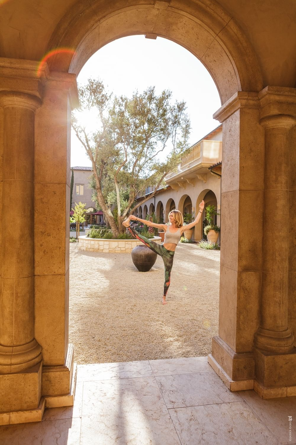 Woman holding a yoga pose in the courtyard