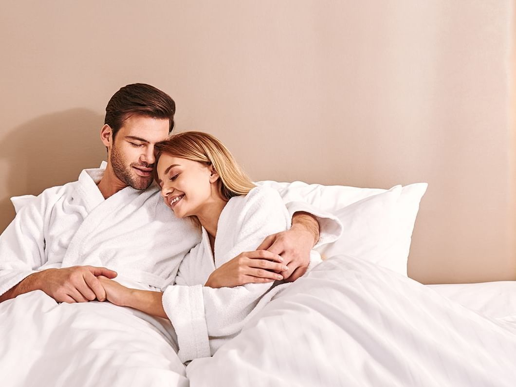 A couple on bed wearing bathrobes at Carriage House Hotel