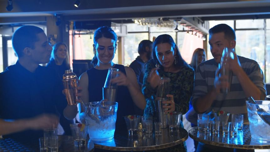 Group of people having fun making cocktails