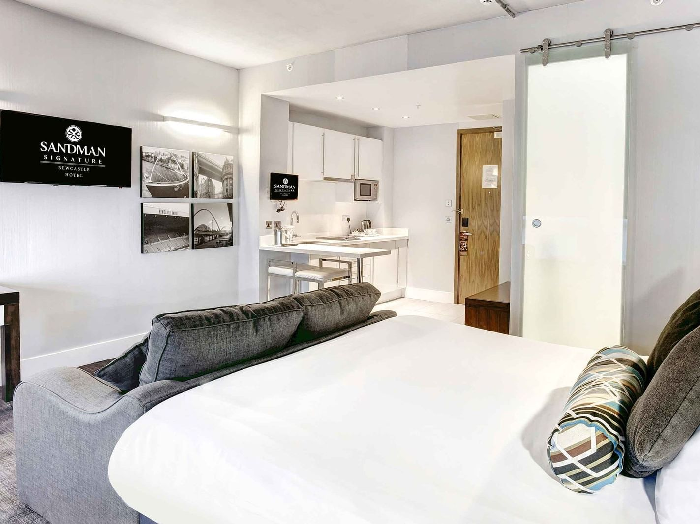 The Corporate King Studio at Sandman Signature Newcastle Hotel with one super king ked (with premium pillow-top), one pull-out sofa bed, a flat-screen tv and small pantry with kitchen supplies and white pantry cupboards on the side