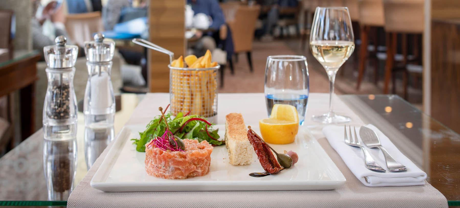 Table with salmon tartar and potato at Warwick Geneva