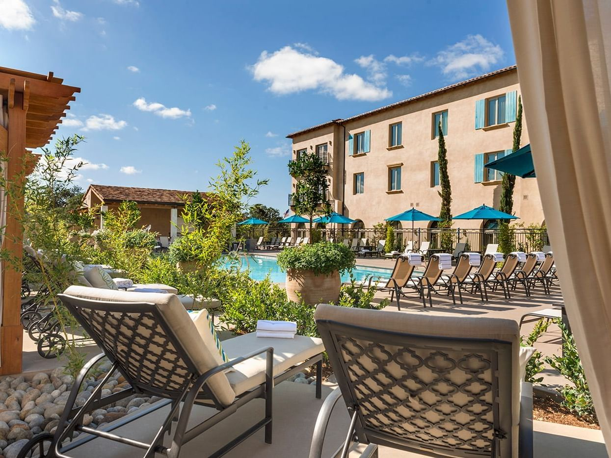 Cabana lounge chairs poolside and exterior view of hotel