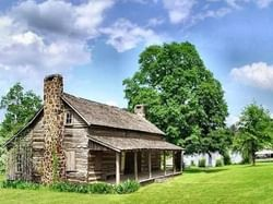 a wooden cottage and lush green trees