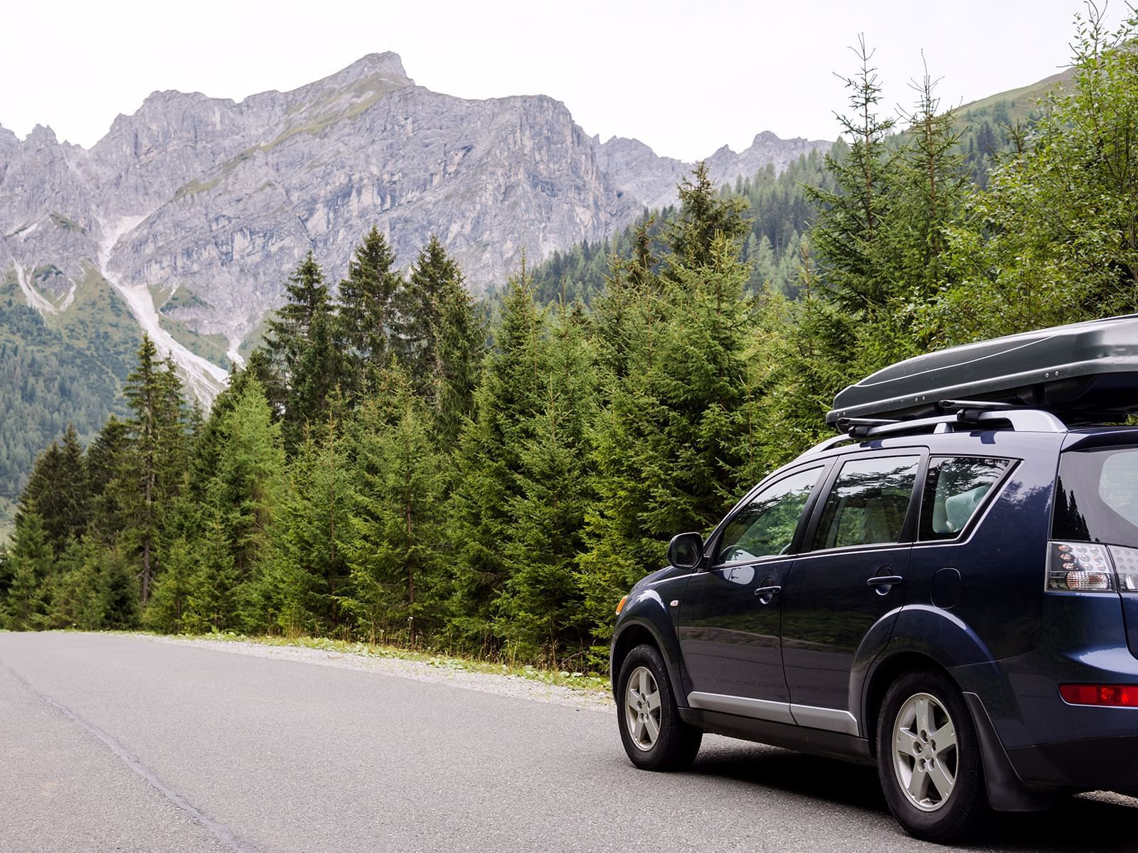 An image of a car on the road near a forest and mountains