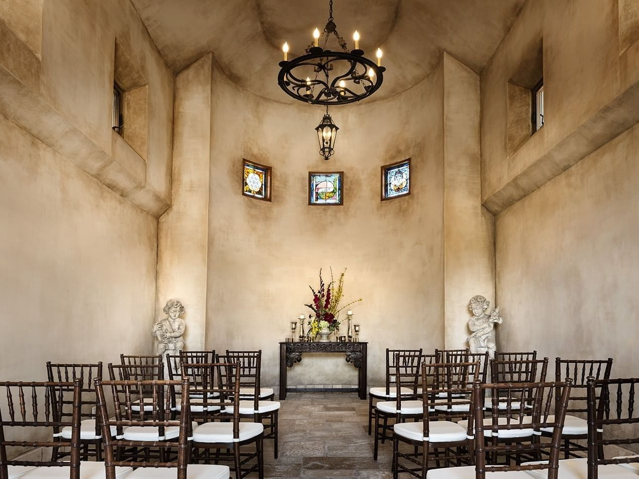 Inside the stucco Abbayy, four rows of chairs set for a small indoor wedding.