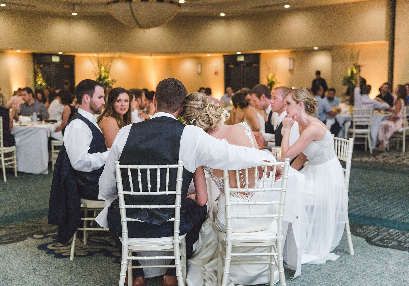 grooms men and brides maids sit at a table