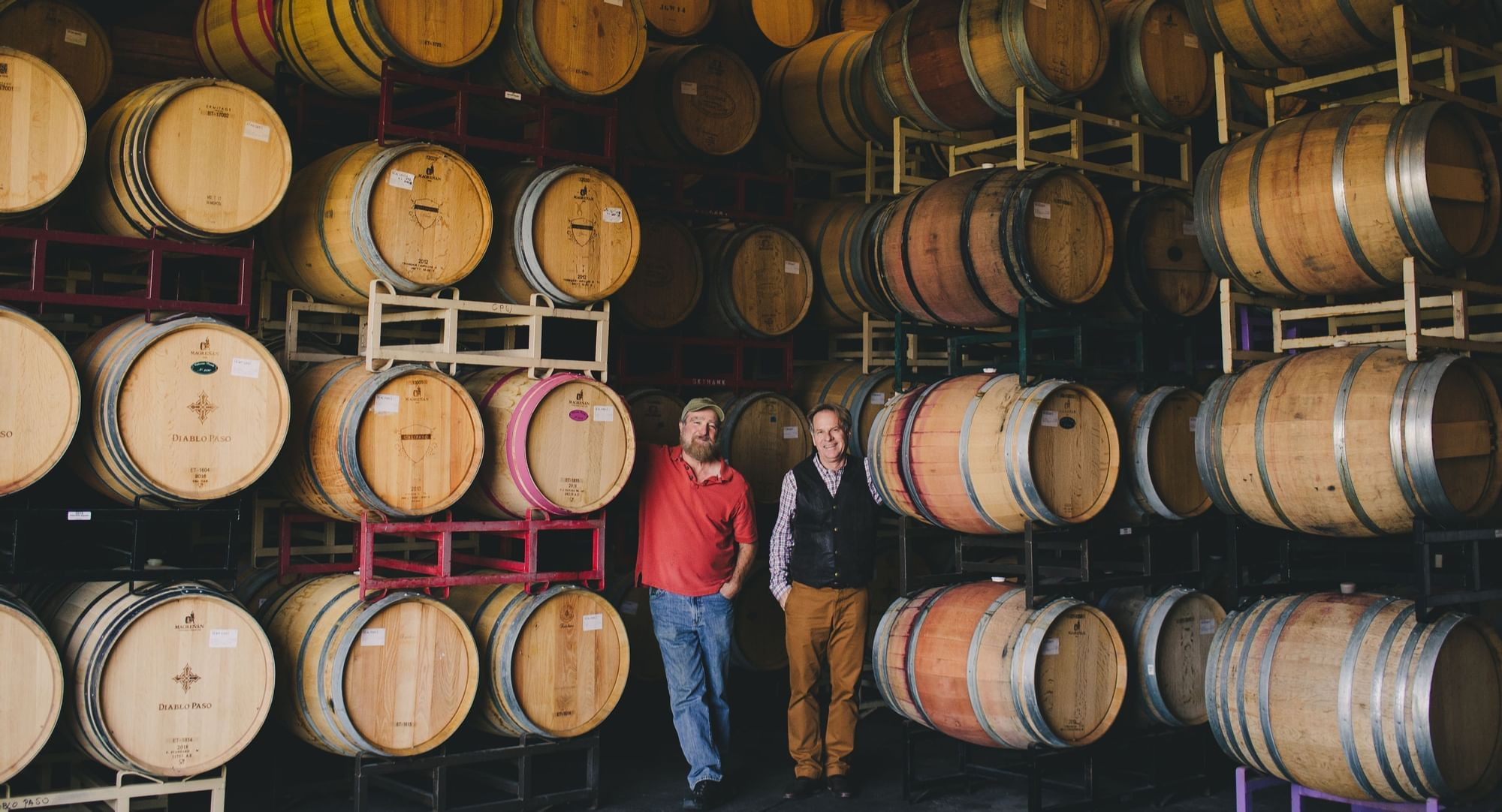 Two men standing by stacks of wine barrels