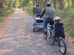 Family riding bicycles in Bruce Freeman Rail Trail near Westford Regency