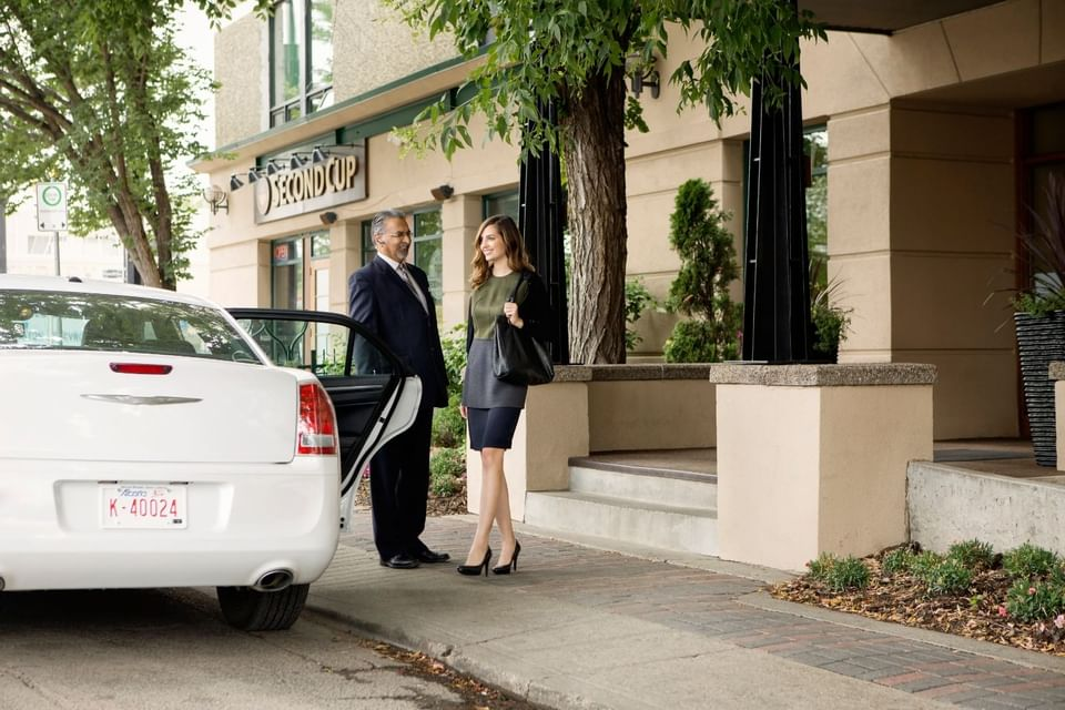 Concierge opens door for a lady at Varscona Hotel on Whyte