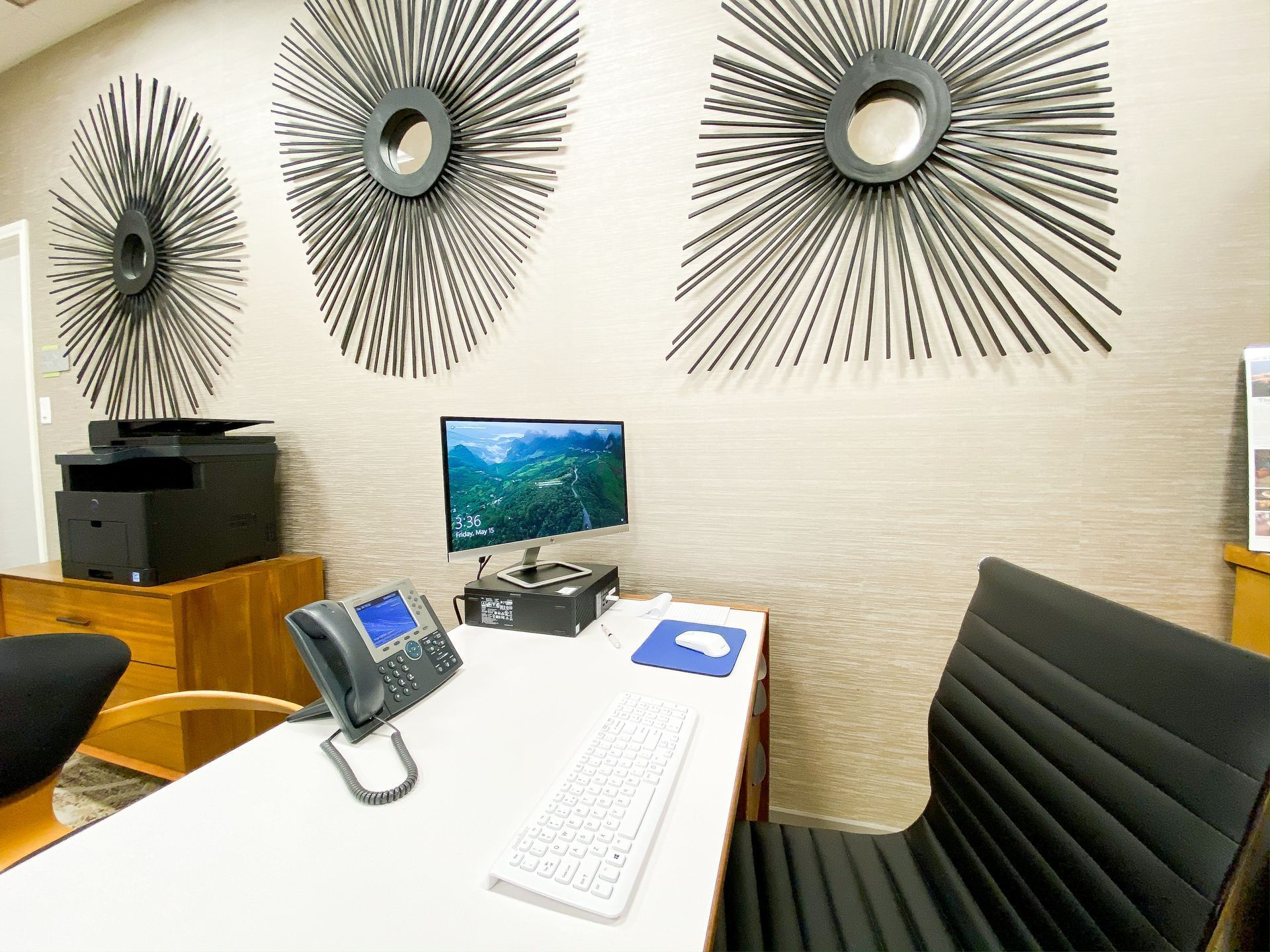 a desk with a computer and phone