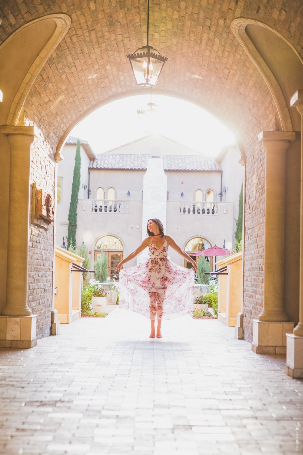 Woman standing under the courtyard archways with arms spread wid