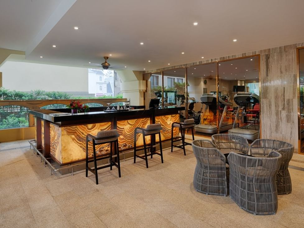 bar counter with three cushion high chairs