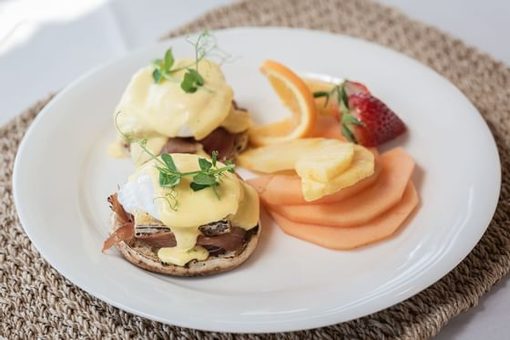 a plate of eggs benedict and sliced fruit