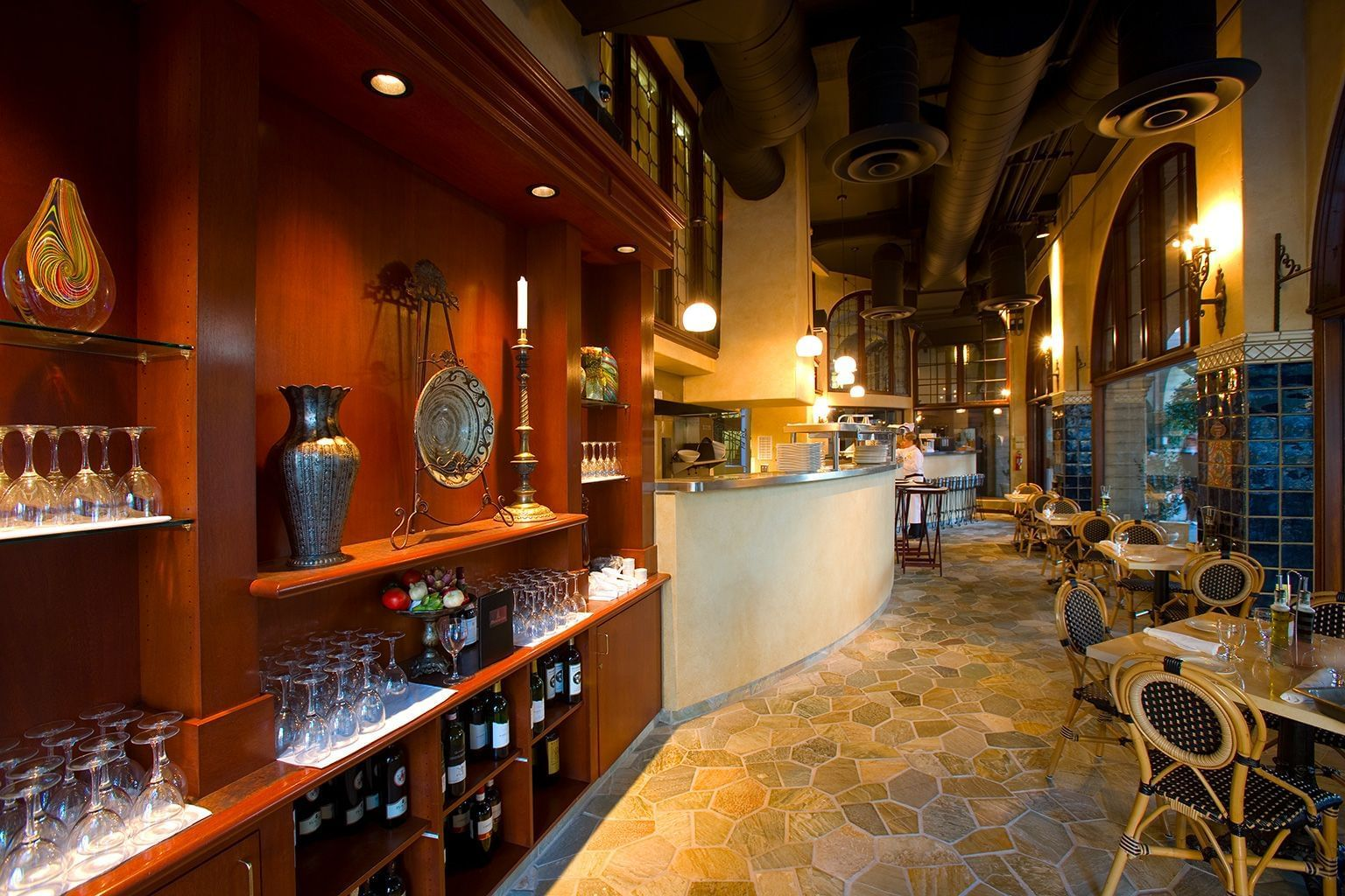 shelves of glasses and wine bottles near dining tables