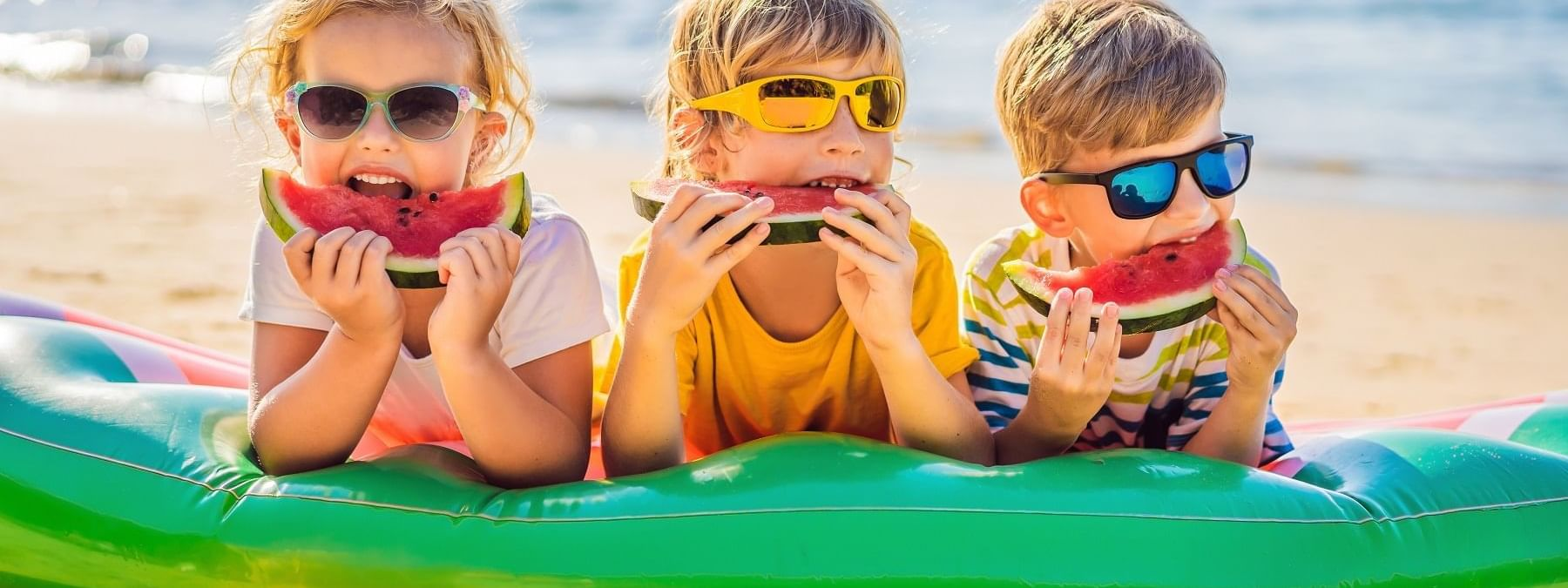 Kids eating watermelon on beach at Daydream Island Resort