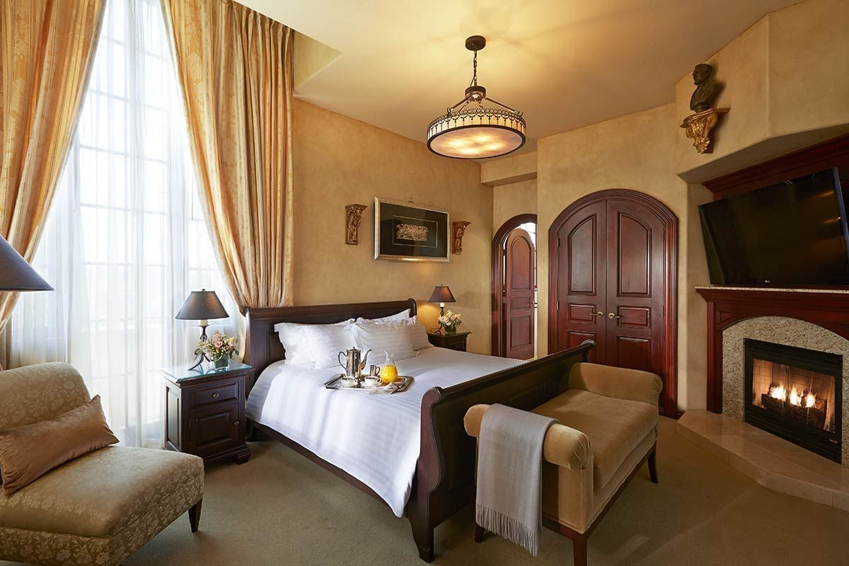 Mission Inn room with bed, accent chair, chaise lounge and firep