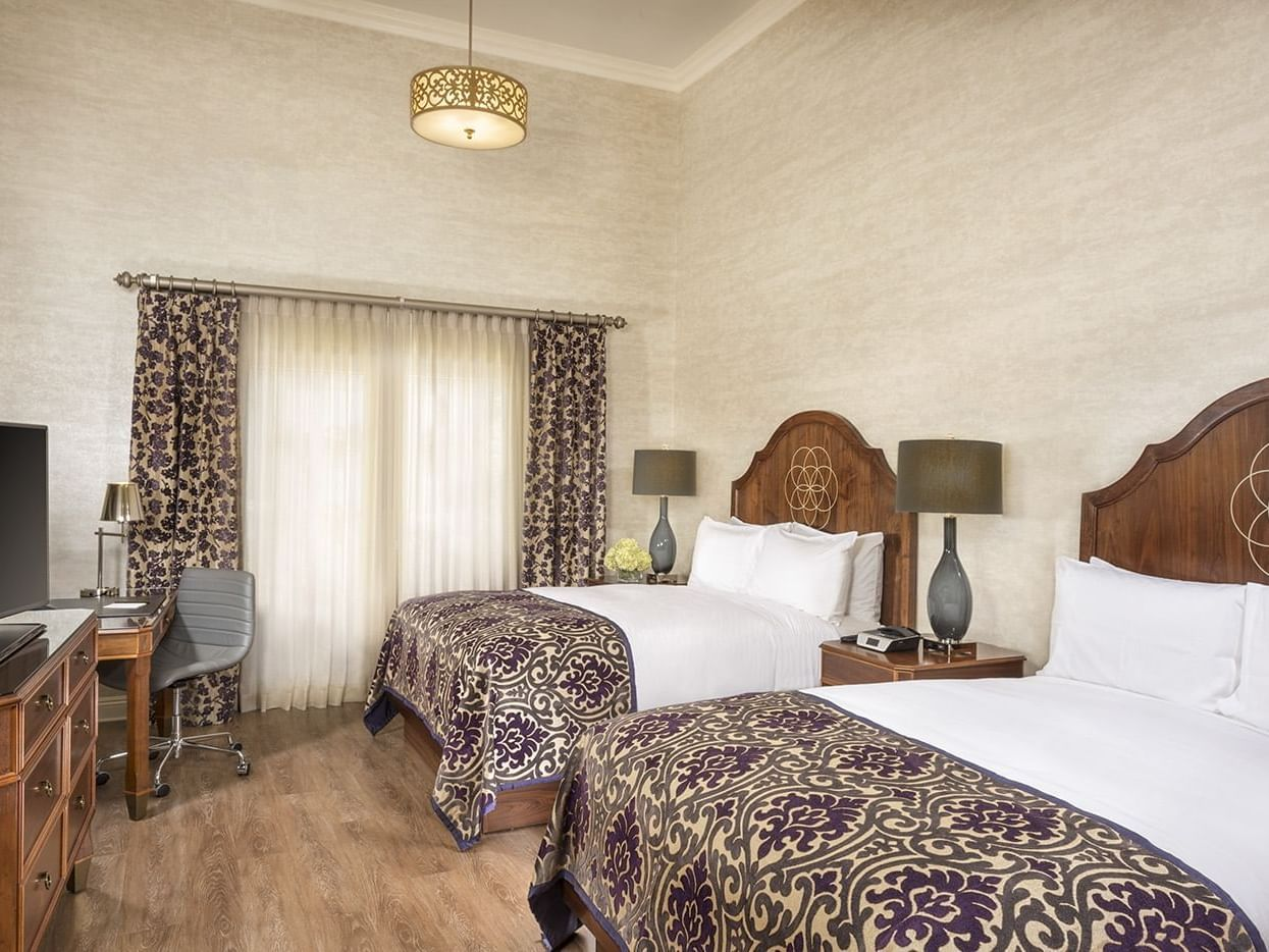 A room which includes Two queen size beds, a writing desk and a flat screen TV.