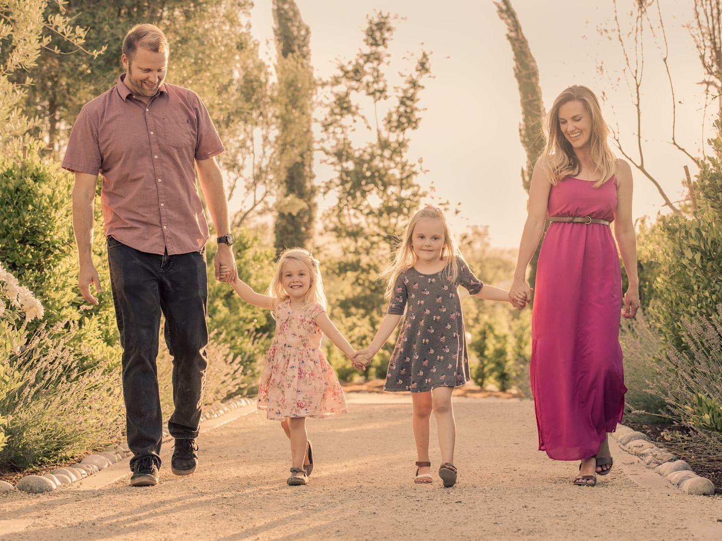 Family of 4 walking through garden