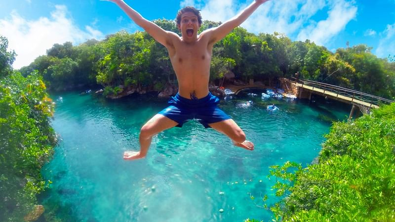A guest jumping into a natural pond near The Reef Resorts