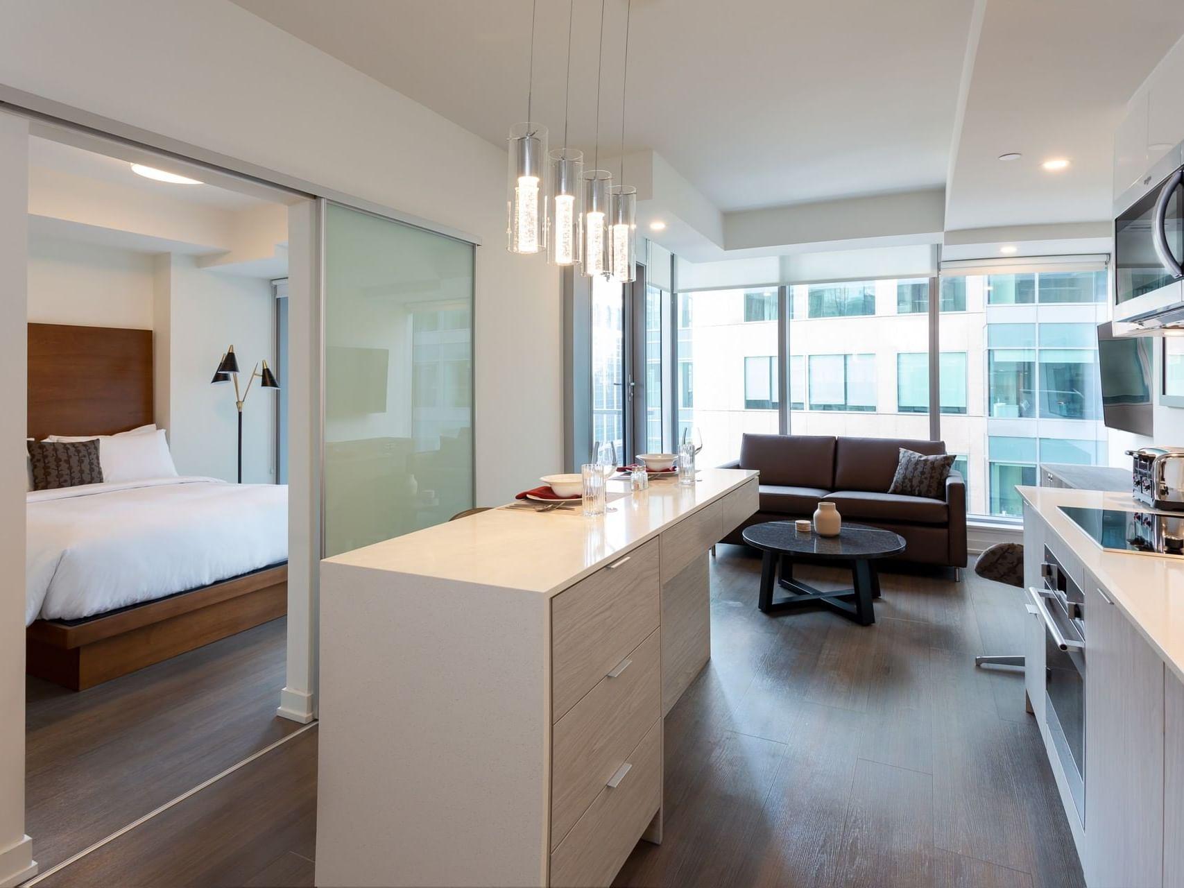open kitchen next to living room and door to bedroom