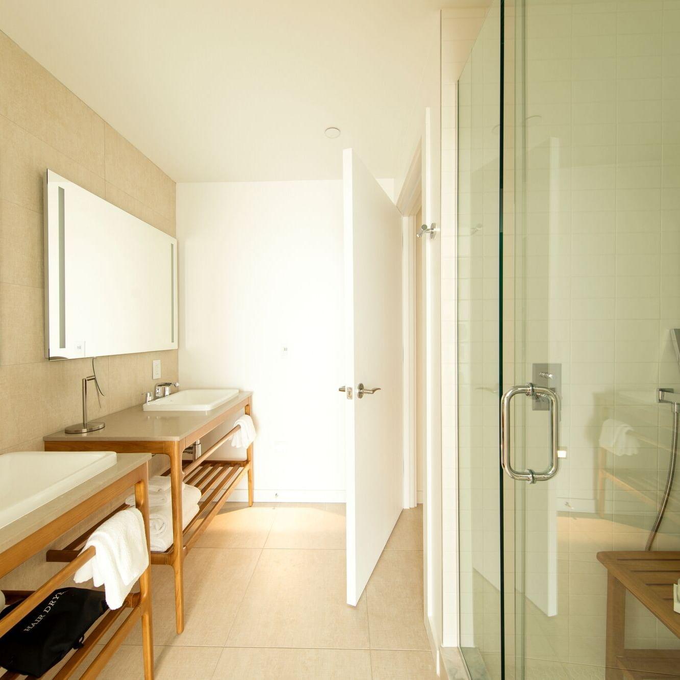 bathroom with double vanities and walk in shower