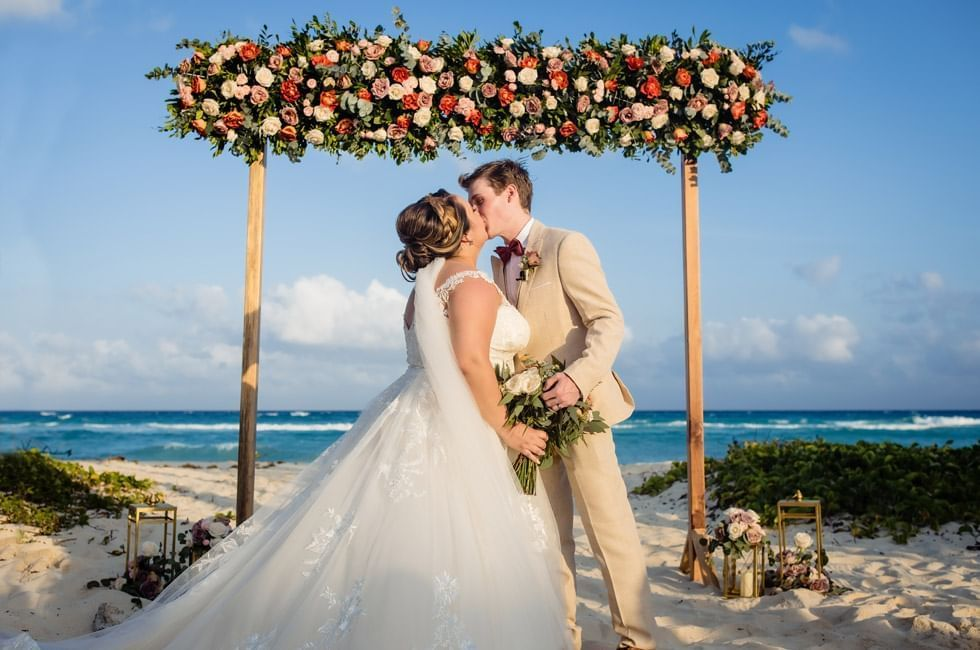 A couple kissing on wedding altar at The Reef Coco Beach