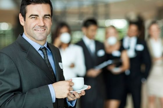 Guy in a business suit drinking coffee