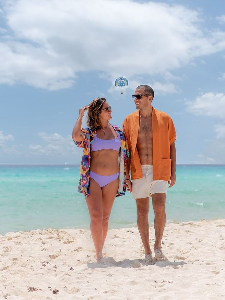 A couple walking on the beach at The Reef Playacar