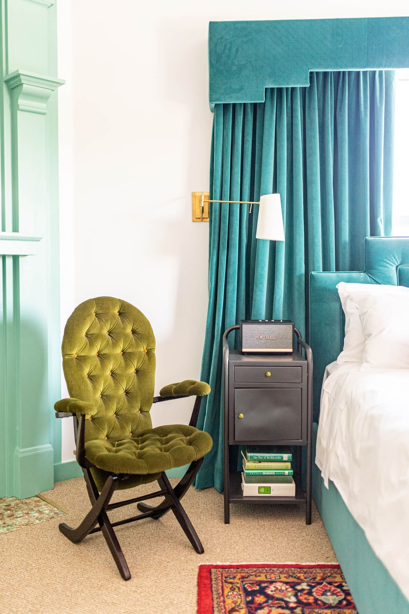 chair next to bed with blue bedframe