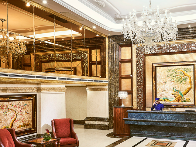 luxurious hotel lobby with reception desk and glass chandelier