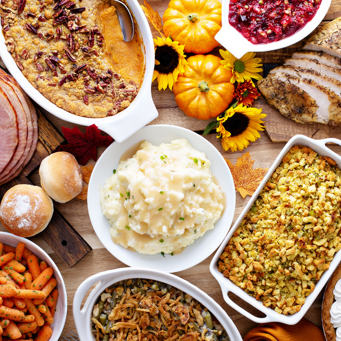 thanksgiving table with turkey, ham, mashed potatoes, stuffing, pie, & fall decor