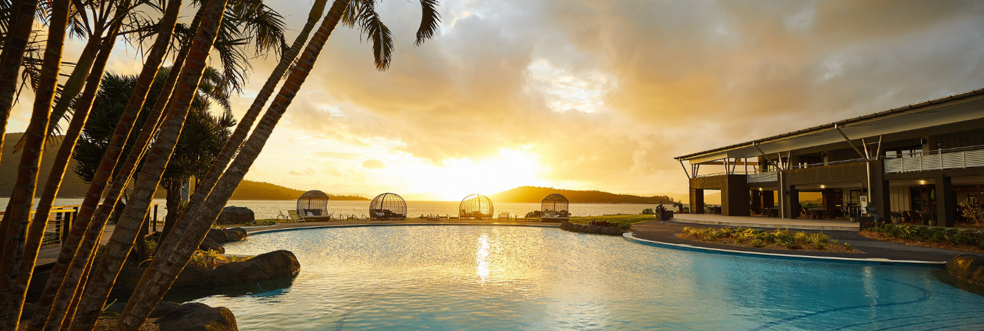 Coconut trees and pool at sunset at Daydream Island Resort