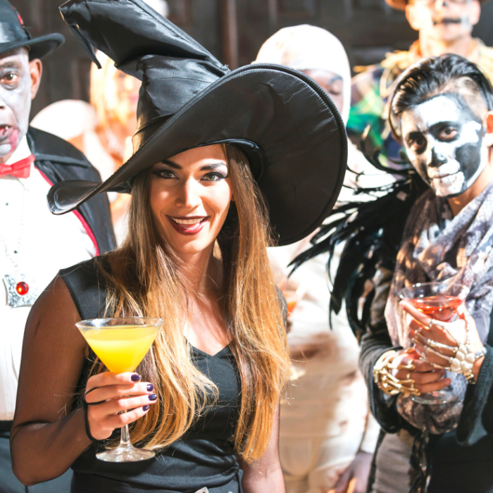 Adults in Halloween Costumes: Vampire, Witch, Skeleton in front. Fairy, Mummy, Scarecrow in back.