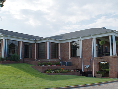 a large brick building with a grassy lawn