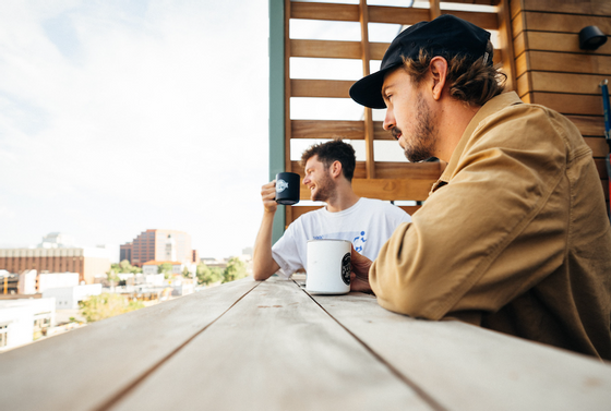 Two people having coffee by the balcony at Kinship Landing