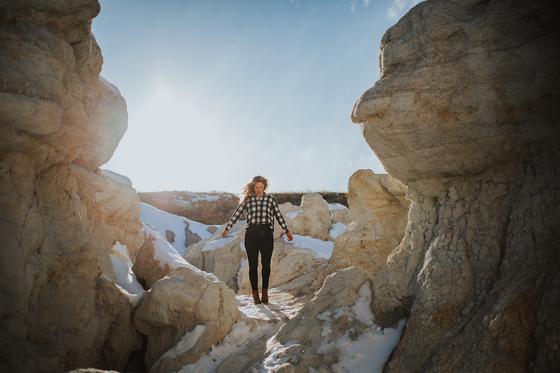 A girl posing among boulders of rocks near Kinship Landing