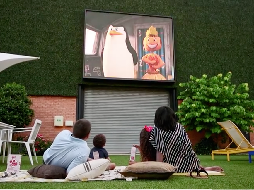 a family watching a moving in a courtyard