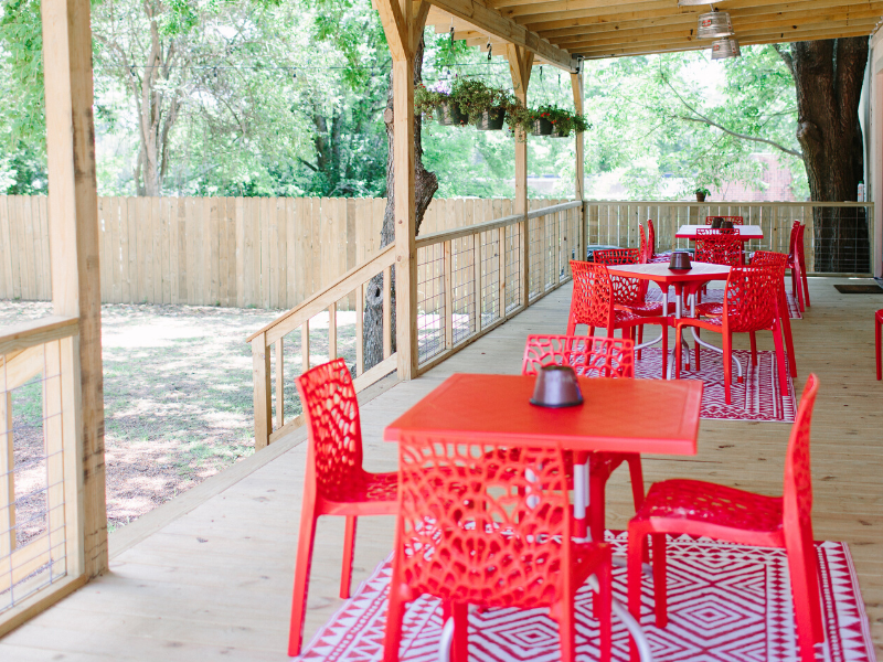 chairs and tables on a wooden porch area